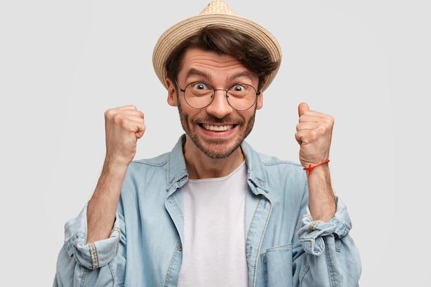 Jonge man met strooien hoed en denim overhemd