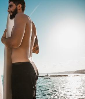 Jonge man met surfplank aan de voorkant in de buurt van de oceaan