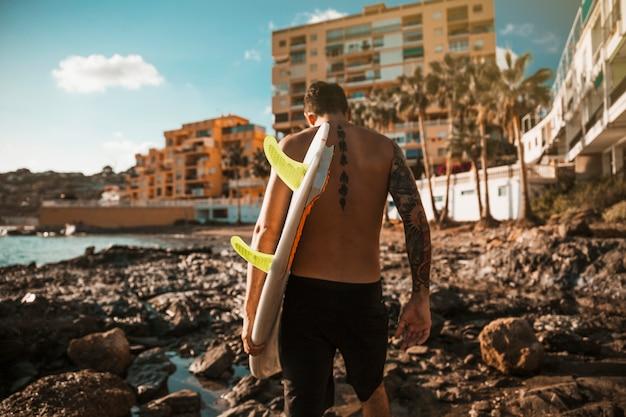Jonge man met surfplank gaan op rots kust in de buurt van water en gebouwen