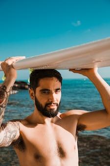 Jonge man met surfplank op hoofd op strand dichtbij overzees en blauwe hemel