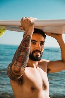 Jonge man met surfplank op hoofd op strand in de buurt van water