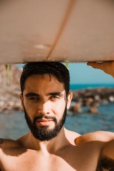 Jonge man met surfplank op hoofd op strand in de buurt van zee