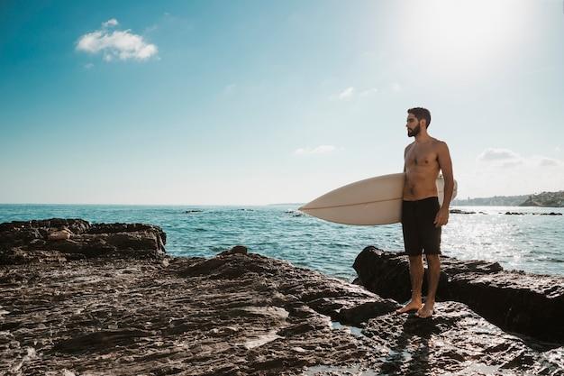 Jonge man met surfplank op steen in de buurt van zee