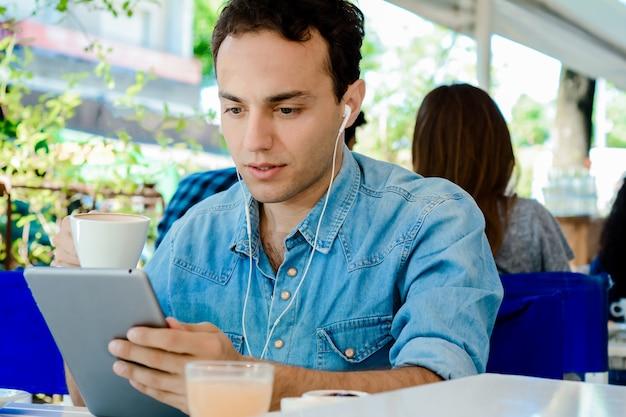 Jonge man met tablet in koffie winkel