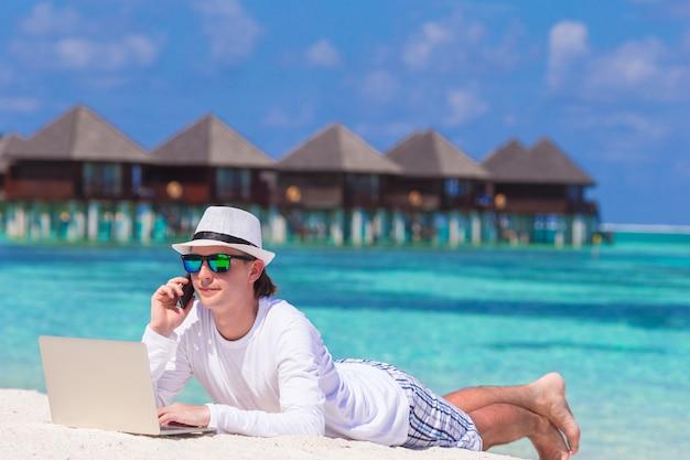Jonge man met tablet pc en mobiele telefoon op tropisch strand