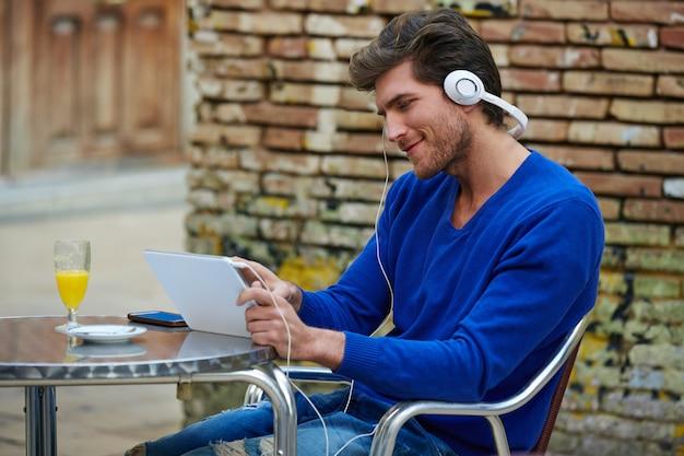 Jonge man met tablet pc touch luisteren muziek