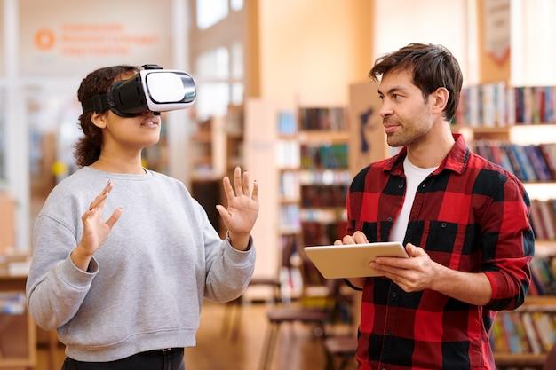 Jonge man met tabletnetwerken terwijl hij zijn klasgenoot in vr-headset bekijkt tijdens interactie