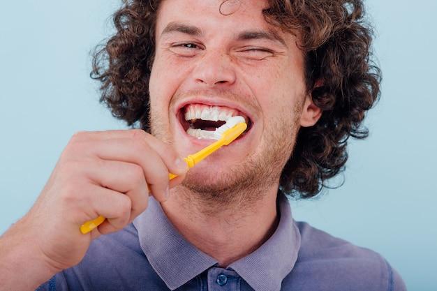 Jonge man met tandenborstel en tandpasta glimlachen