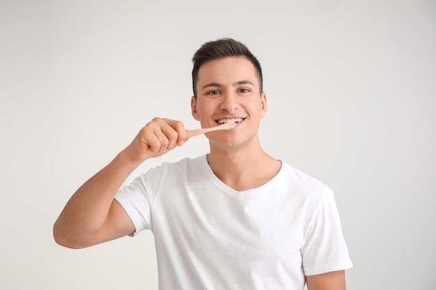 Jonge man met tandenborstel op grijs