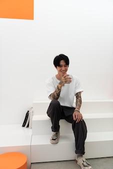 Jonge man met tatoeages genietend van een kopje koffie bij koffiehuis