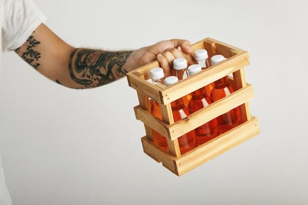Jonge man met tatoeages houdt een doos oranje frisdrank in flessen zonder label, close-up geïsoleerd op wit