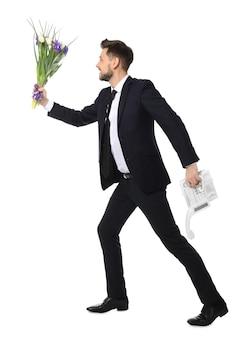 Jonge man met telefoon en bloemen aan het rennen