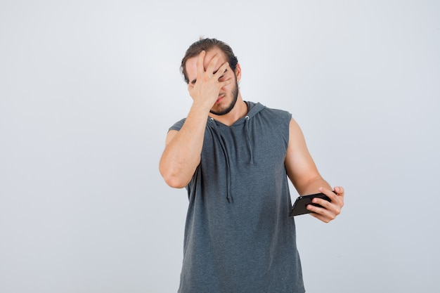 Jonge man met telefoon in de hand, gezicht bedekt met hand in t-shirt met een kap en op zoek ongelukkig, vooraanzicht.
