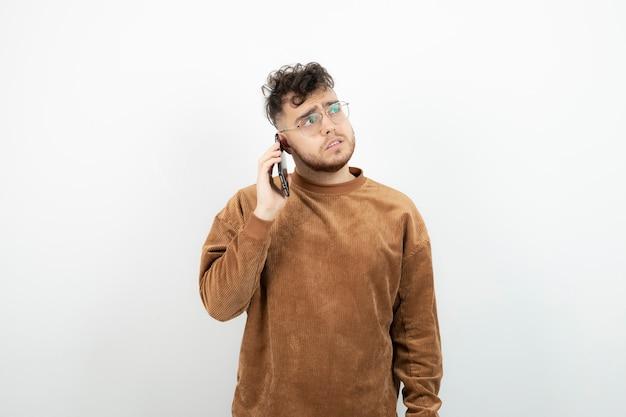 Jonge man met telefoontje over witte muur.