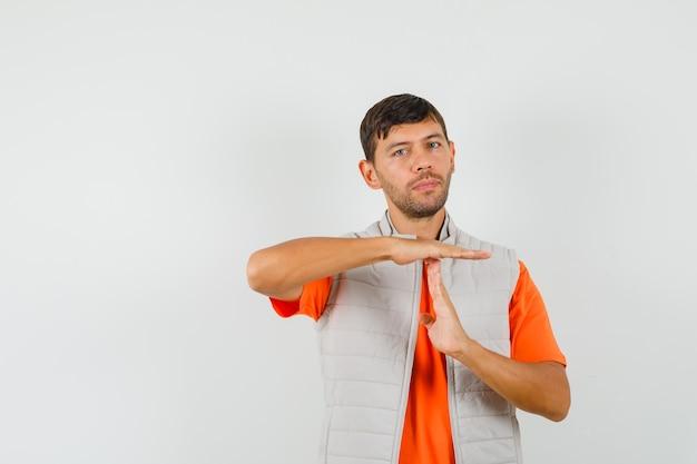 Jonge man met tijdonderbreking gebaar in t-shirt, jasje