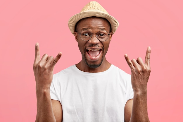 Jonge man met trendy bril en strooien hoed
