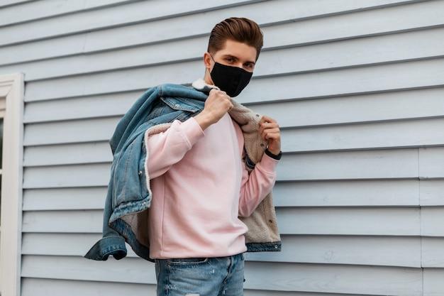 Jonge man met trendy kapsel in spijkerjasje in roze sweatshirt met beschermend zwart masker poseert in de buurt van witte muur op straat. mode tiener man in masker is beschermd tegen virussen. gezonde levensstijl.