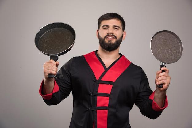 Jonge man met twee donkere pannen in handen.