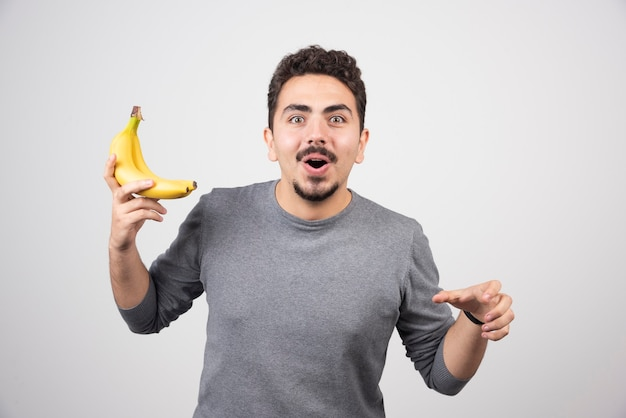 Jonge man met twee rijpe bananen op grijs.