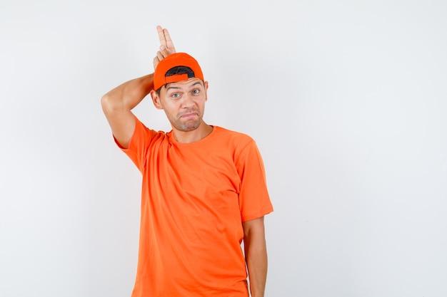 Jonge man met twee vingers achter het hoofd als hoorn in oranje t-shirt en pet en ziet er grappig uit
