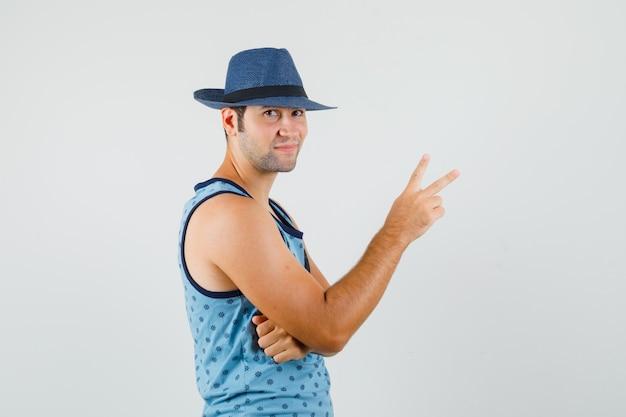 Jonge man met v-teken in blauw hemd, hoed en op zoek zelfverzekerd.