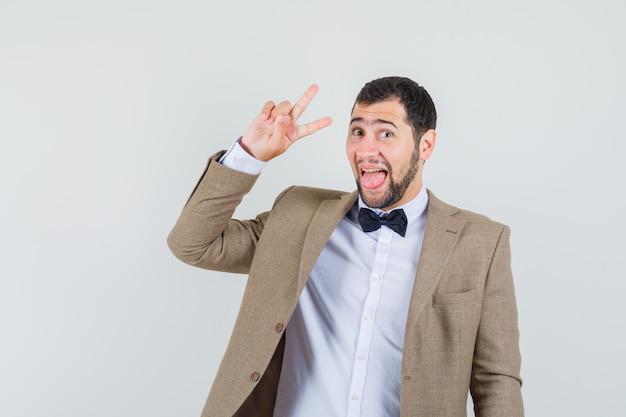 Jonge man met v-teken, tong uitsteekt in pak en er energiek uitziet. vooraanzicht.