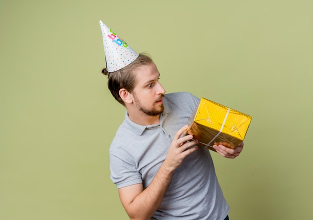 Jonge man met vakantie glb bedrijf verjaardagscadeau kijken verrast verjaardagsfeestje concept staande over lichte muur