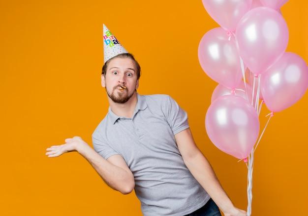 Jonge man met vakantie pet vieren verjaardagsfeestje houden bos ballonnen kijken verrast en verbaasd staande over oranje muur