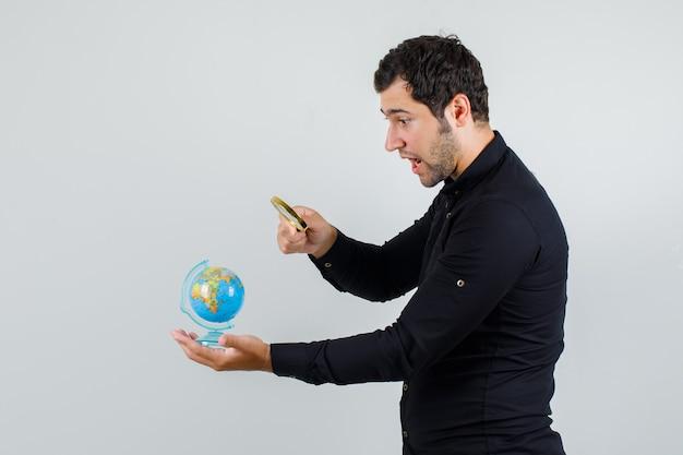 Jonge man met vergrootglas over wereldbol in zwart shirt en op zoek verrast