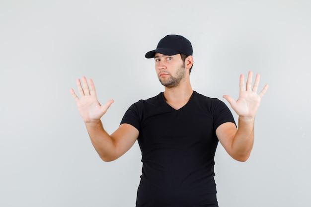 Jonge man met verhoogde handpalmen in zwart t-shirt