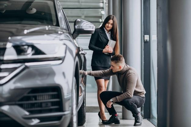 Jonge man met verkoopster bij een autotoonzaal
