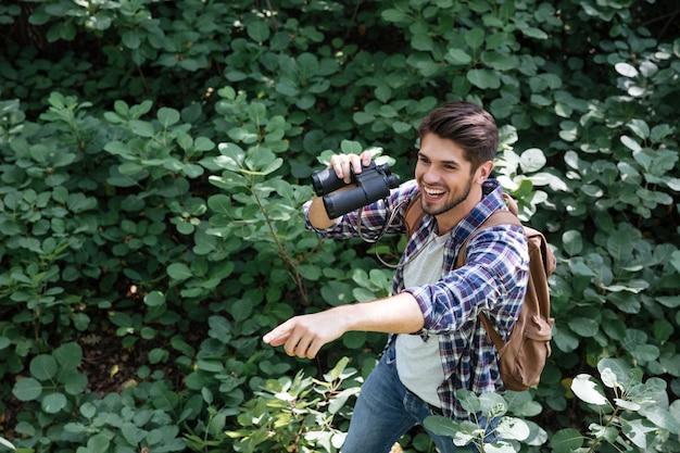 Jonge man met verrekijker in het bos laat ons zien