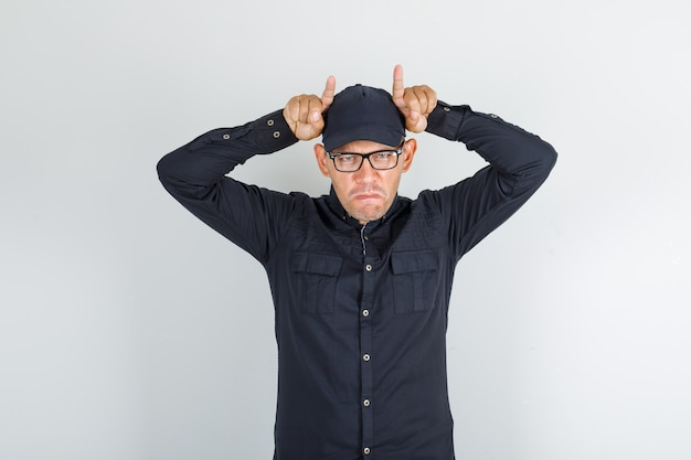 Jonge man met vinger boven het hoofd gebaren als hoorns in shirt en pet, bril en grappig op zoek