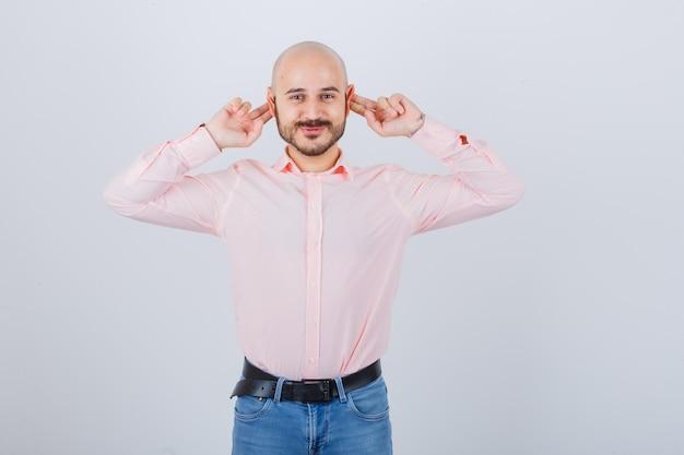 Jonge man met vingers achter de oren