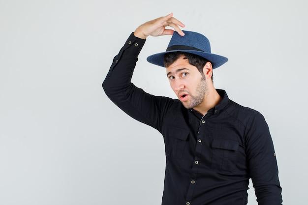 Jonge man met vingers op hoed in zwart shirt