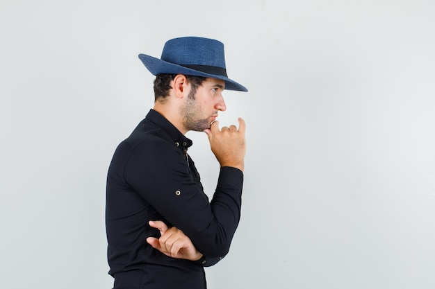 Jonge man met vingers op kin in zwart shirt