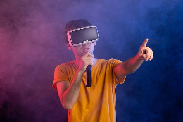 Jonge man met virtual reality headset en mic donkerblauw oppervlak vast te houden