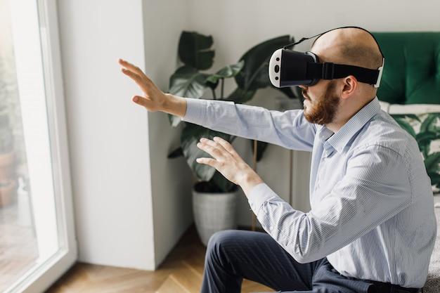 Jonge man met virtual reality headset speelt thuis in een videogame.