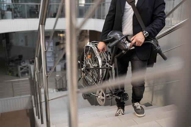 Jonge man met vouwfiets op roltrap
