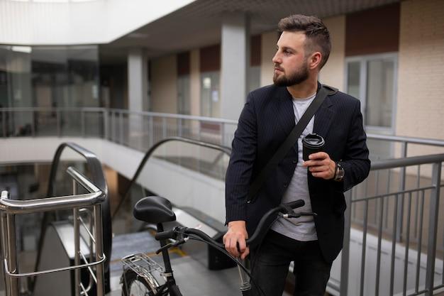Jonge man met vouwfiets op roltrap Gratis Foto