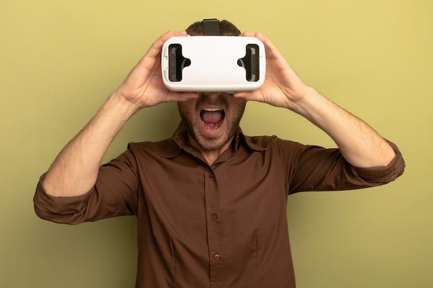 Jonge man met vr-headset grijpen het kijken naar voorkant schreeuwen geïsoleerd op olijfgroene muur