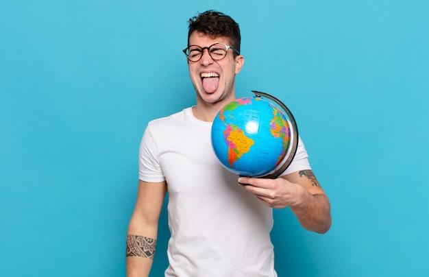 Jonge man met vrolijke, zorgeloze, rebelse houding, grappen maken en tong uitsteken, plezier maken