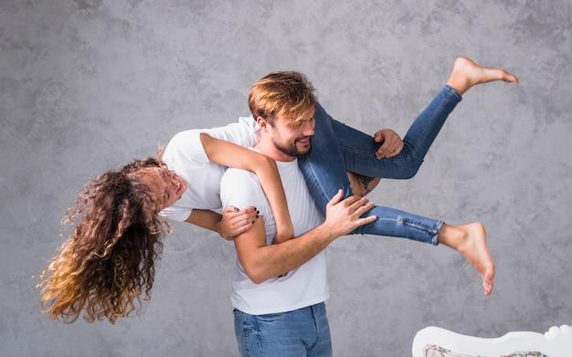 Jonge man met vrouw op schouder
