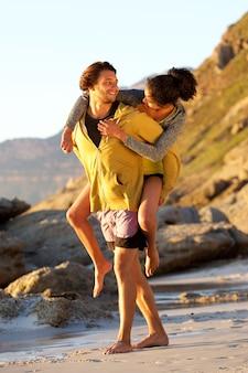 Jonge man met vrouw op zijn rug op het strand