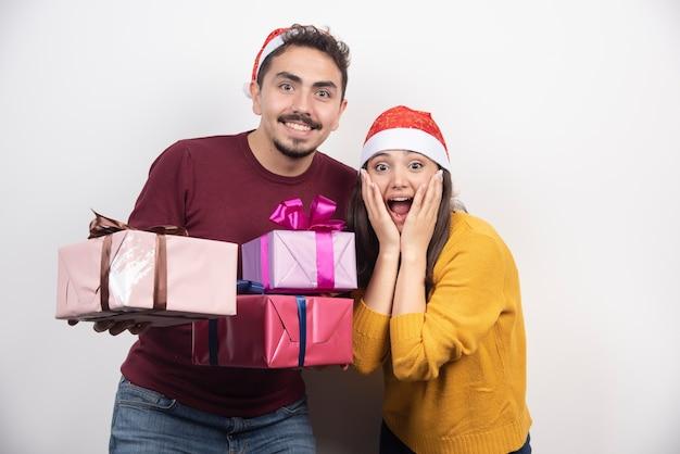 Jonge man met vrouw poseren met kerstcadeautjes.
