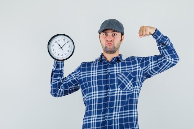 Jonge man met wandklok, spieren in shirt, pet tonen en er zelfverzekerd uitzien. vooraanzicht.