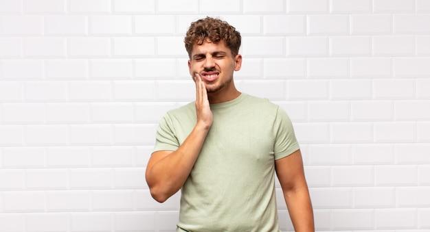 Jonge man met wang en pijnlijke kiespijn lijden