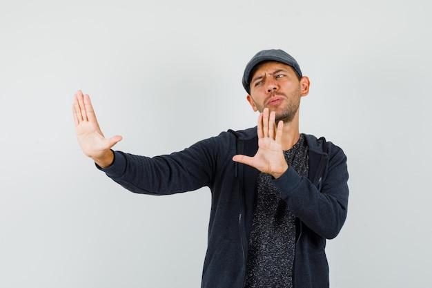 Jonge man met weigering gebaar om zichzelf te beschermen in t-shirt, jasje, pet