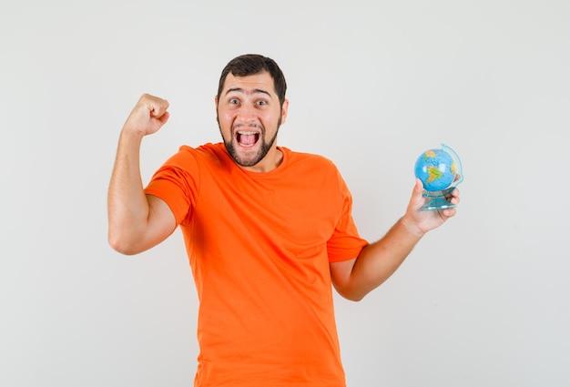Jonge man met wereldbol met winnaargebaar in oranje t-shirt en er gelukkig uit. vooraanzicht.
