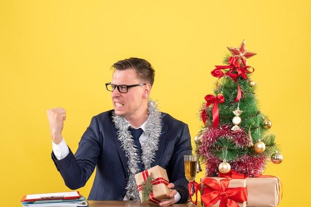 Jonge man met winnende gebaar zittend aan de tafel in de buurt van kerstboom en presenteert op geel